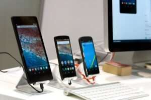 three smart phones and a computer